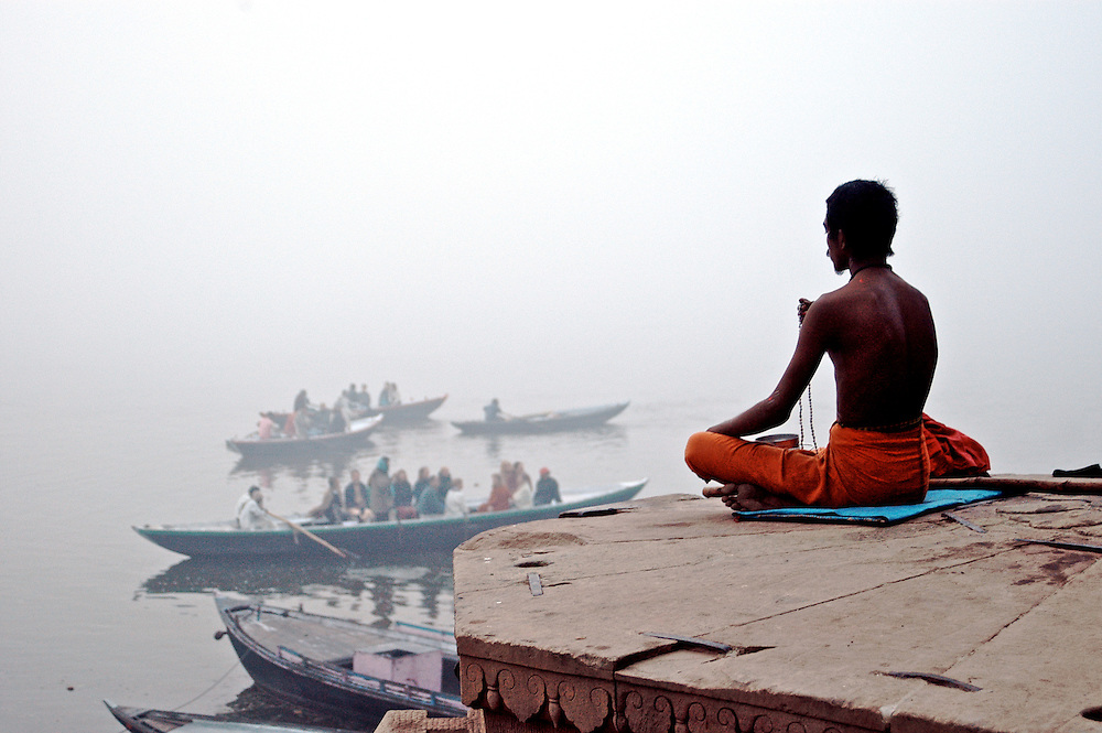 A man contemplates on a platform overlooking the Ganges River in Varanasi, India while boatloads of tourists pass by.