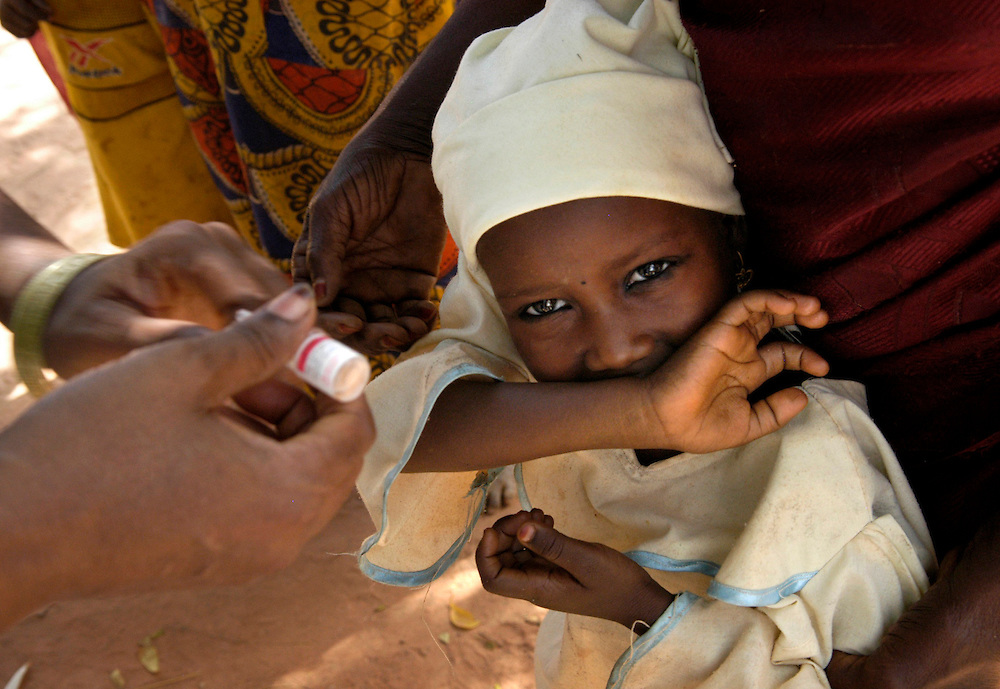 "Vaccinator Aisha Rumfa coos ""hoo baby, sweet sweet,"" to urge an reluctant child to open her mouth for oral polio vaccine near Ungogo, Nigeria, where villagers refused to accept the vaccine last year because they wanted the government to also give them a new water system."