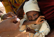 """Vaccinator Aisha Rumfa coos """"hoo baby, sweet sweet,"""" to urge an reluctant child to open her mouth for oral polio vaccine near Ungogo, Nigeria, where villagers refused to accept the vaccine last year because they wanted the government to also give them a new water system."""