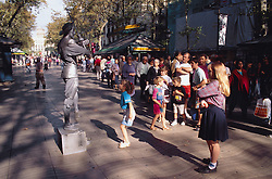 Crowd of people walking along street in Las Ramblas; Barcelona; some watching mime artist performing on podium,