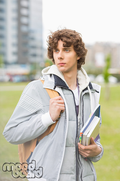 Young male university student holding textbooks at campus
