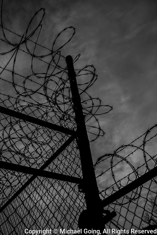 Black & white photo of razor and barbed wire shot from extreme up angle against ominous sky background.