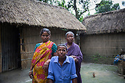 Shankor Rani, 32, sits with his wife Gita Rani, 26, and his mother Dhonobala Rani 70, behind in the courtyard of their house.<br /> <br /> Living in Ponchoki Bhajini village located inside the enclave of Dhoholakhagrabari, Shankor Rani missed the Indian verification registration in 2011 who came to take details of everyone who lives in the enclaves in Bangladesh and those that want to leave. As a result his wife, child and himself cannot be included and is not allowed to move to India with the rest of his family including his mother.<br /> <br /> On July 31st 2015 the enclaves that formed one of the world's most complicated borders were officially absorbed in to the countries that surrounded them in a land-mark land swap between India and Bangladesh. The people that lived in them will finally receive citizenship.<br /> <br /> Enclaves are small pockets of sovereign land completely surrounded by another sovereign nation. Approximately 160 enclaves, known as chitmahals, exist on either side of the India-Bangladesh border. For 68 years the 50,000 plus inhabitants of these enclaves have lived a difficult existence, stranded from their home nation and ignored by the country that surrounds them. <br /> <br /> In theory even leaving their enclaves is illegally crossing an international border and for decades it has been very difficult for them to receive even the most basic of rights whether education or health. Even the police have no jurisdiction in the enclaves leaving them essentially lawless.