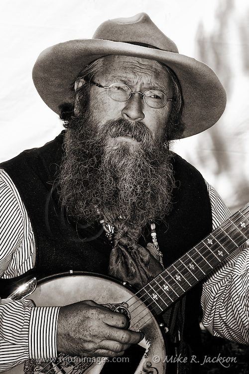 Bearded banjo picker at a Mountain Man Rendezvous in West Yellowstone, Montana.