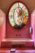 The ornate stained glass window in a large pink bathroom located in a mansion built in 1926.
