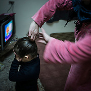 A syrian woman prepares her daughter for the night, on december 22nd 2013 in their appartment in the suburbs of Irbid.
