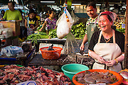 "26 SEPTEMBER 2012 - BANGKOK, THAILAND:  A meat vendor in Khlong Toey Market in Bangkok. Khlong Toey (also called Khlong Toei) Market is one of the largest ""wet markets"" in Thailand. The market is located in the midst of one of Bangkok's largest slum areas and close to the city's original deep water port. Thousands of people live in the neighboring slum area. Thousands more shop in the sprawling market for fresh fruits and vegetables as well meat, fish and poultry.    PHOTO BY JACK KURTZ"