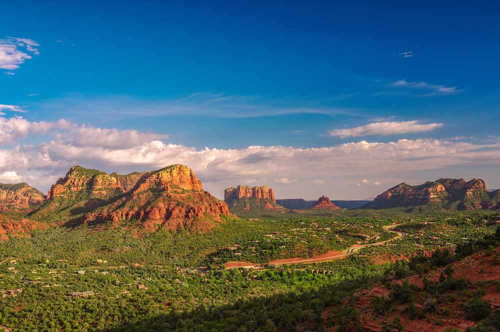 The sun begins to set over the red rock formations surrounding Sedona, Arizona.
