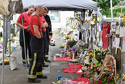 © Licensed to London News Pictures. 23/06/2017. London, UK. Firefighters pay their respects at a nearby memorial dedicated to the victims of the fire.  Nine days on, police have reported that the Grenfell Tower fire in west London started in a fridge-freezer, and outside cladding and insulation failed safety tests. Photo credit : Stephen Chung/LNP