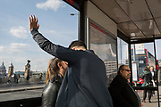 Lovers kiss in a bus stop at the southern end of London Bridge, on 19th April, in the City of London, England.