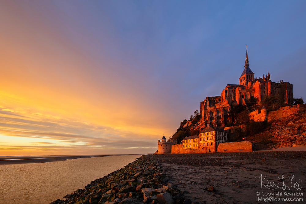 """The golden light of sunset colors the walls of Mont Saint-Michel, a former monastery on a tidal island in Normandy, France. Mont Saint-Michel was known as Mont-Tombe until the 8th century when St. Aubert built a church there after having a vision of the archangel St. Michael. It soon became a pilgrimage center and a Benedictine abbey was built there in 966. After it was partially burned in 1203 during a takeover attempt by King Philip II of France, a monastery, known as La Merveille (""""The Wonder""""), was built and later fortified. The Mont Saint-Michel monastery was dissolved during the French Revolution (1787–99) and became a prison under Napoleon's reign before the site was restored as a historic monument in 1874. Mont Saint-Michel was designated a UNESCO World Heritage site in 1979. Mont Saint-Michel lies at the mouth of the Couesnon River, which is visible at on the left side of the image. Mont Saint-Michel is cut off from the mainland by sea water during very high tides."""
