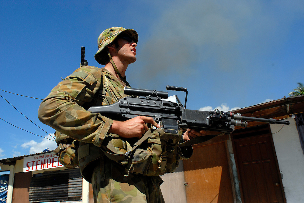 An Australian soldier patrols past a burning building in Dili. 03/06/06
