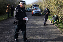 Denham, UK. 11 February, 2020. A Thames Valley Police officer walks with a book entitled 'Counter Terrorism Policing' after issuing a warning using it to an environmental activist from Extinction Rebellion who had been 'slow walking' in front of a truck delivering a JCB forklift truck to a HS2 site. The activist was subsequently arrested.