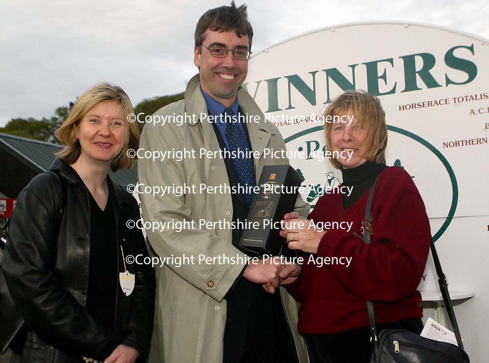 Famous Grouse day at the races..15.05.02<br />The owner of Thistlekicker Mrs D Thomson who won the Highland Park 12 year old Single Malt conditional jockeys selling handicap hurdle race recievesher prize from Alison Lowson Editor of the Perthshire Advertiser and Gordon Bannerman, sports writer with the Perthshire Advertiser<br /><br />For details please contact Emrys Inker at the Edrington Group on 01738 493781<br /><br />Pic by Graeme Hart<br />Copyright Perthshire Picture Agency<br />Tel: 01738 623350 / 07990 594431