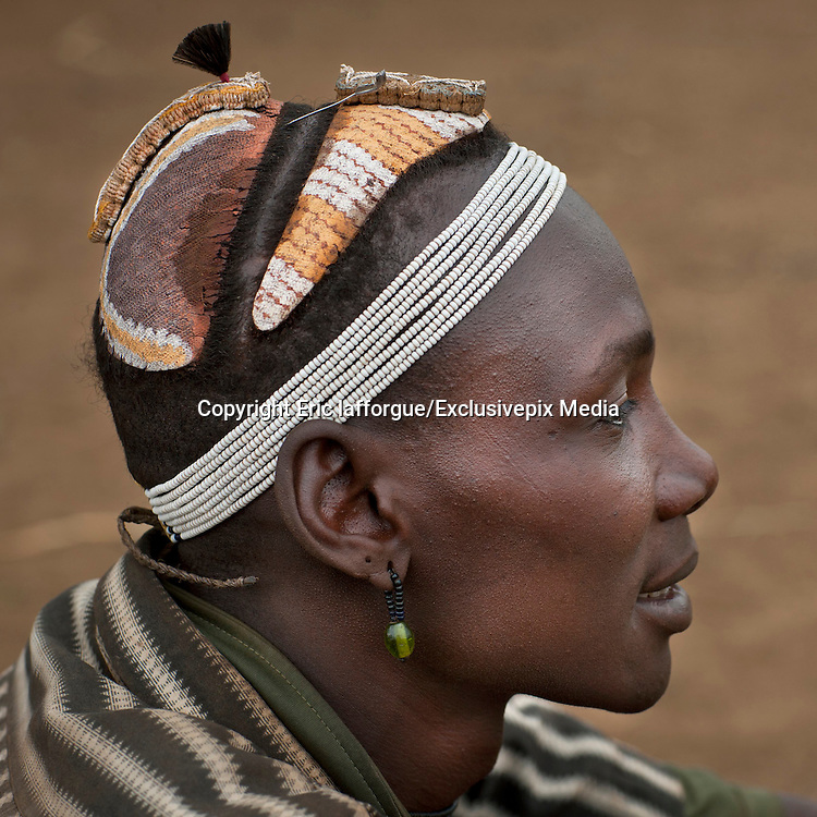 Ethiopian Tribe Recycles Modern Worldís Discards Into Fashion Accessories<br /><br />The Daasanach are a semi-nomadic tribe numbering approximately 50,000 individuals who live in the Omo Valley in southern Ethiopia. In the past, the tribe roamed from place to place herding livestock around open areas according to the seasons and the changing availability of water. But over the last fifty years, having lost the majority of their lands, they have also grown dependent to agriculture. Like many tribes in the region, the Daasanach have moved to areas closer to the Omo River, where they attempt to grow enough crops to survive.<br /><br />French photographer Eric Lafforgue has spent several years documenting the life and culture of these people, and how they have changed under the influence of modern manufactured goods. An interesting fashion trend amongst the Dassanach is their elaborate headgear, which they make from the strangest of materials  bottle caps, wristwatches, hairclips, and other discarded pieces of plastic and metal.<br />The Daasanach spend months collecting bottle caps and scratching around for cash to pay for broken watches, which the women makes into jewelry and wigs. These are worn by both men and women, young and old.<br /><br />Younger girls and children get the most basic version of the wig, while the oldest women are treated to the heaviest numbers with the most embellishment.<br />Men are only allowed to wear the bottle top wigs until they marry - after that, they create small clay headpieces decorated with a colourful harlequin pattern and enlivened with a feather, although the latter is only allowed after a hunt or a successful clash with an enemy.<br /><br />The young men love to wear necklaces and earrings while the girls have bigger muscles because they do the most difficult work like carrying water, To prevent their headgears from getting spoiled while they sleep (apparently, they never take them off).<br />©Eric lafforgue/Exclusivepix Media