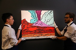 "© Licensed to London News Pictures. 27/09/2019. London, UK. Technicians hold Andy Warhols's artwork titled ""Vesuvius"" - Est - £280,000 - £350-000 during the preview of Sotheby's Frieze Week Contemporary Art Sale. The auction will take place on 3rd October 2019.  Photo credit: Dinendra Haria/LNP"