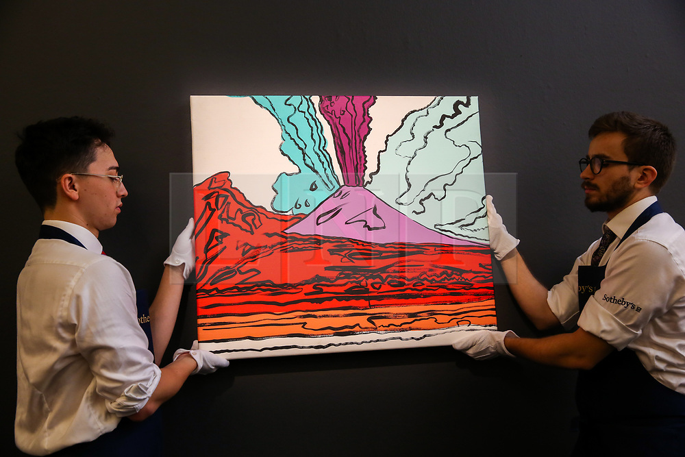 """© Licensed to London News Pictures. 27/09/2019. London, UK. Technicians hold Andy Warhols's artwork titled """"Vesuvius"""" - Est - £280,000 - £350-000 during the preview of Sotheby's Frieze Week Contemporary Art Sale. The auction will take place on 3rd October 2019.  Photo credit: Dinendra Haria/LNP"""