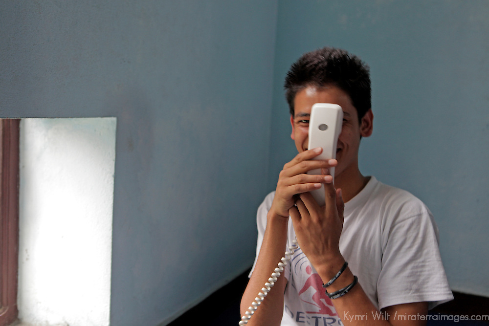 Asia, Nepal, Kathmandu. A young teen embarrased making a phone call.