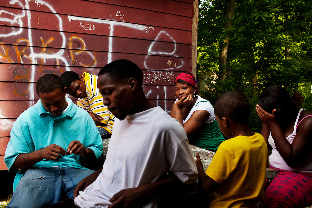 "Lorenzo ""Redd"" Taylor (L) rolls a blunt while hanging out with ""Money Mike"" Campbell, Trell Terry, 17, Debbie Campbell and two others at the abandoned building next to Hoover's corner store in the Baptist Town neighborhood of Greenwood, Mississippi on Wednesday, May 19, 2010."