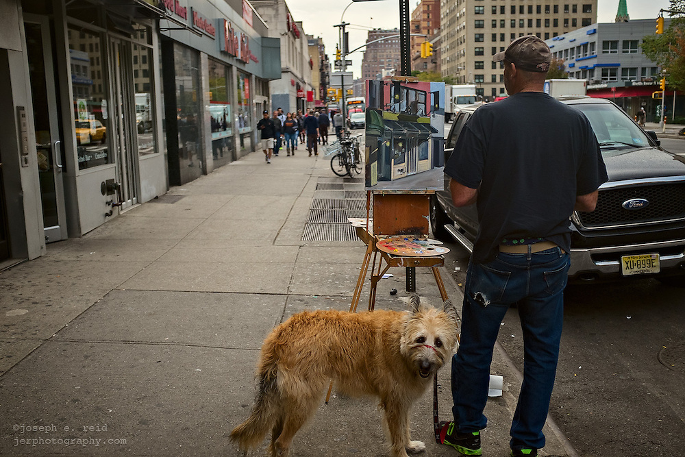 Man with dog on sidewalk painting picture of storefront, New York, NY, US