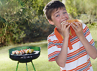 Portrait of boy (10-12) eating frankfurter barbecue grill in background