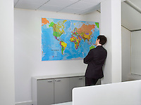 Businessman studying world map in office