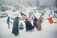 Veterans and tribal leaders return to Oceti Sakowin after marching along Highway 1806 as heavy snow and wind hit the area where thousands have gathered to protest the Dakota Access Pipeline. With the North Dakota winter setting in, protestors at the Oceti Sakowin Camp have dug in as the pipeline, which they have been protesting since early 2016, nears completion at the confluence of the Missouri and Cannonball Rivers.<br /> <br /> <br /> An arcade of flags whip in the wind, welcoming visitors to the Oceti Sakowin Camp, where thousands have come to protest an oil pipeline. Each banner represents one of the more than 300 Native American tribes that have flocked to North Dakota in what activists are calling the largest, most diverse tribal action in at least a century, perhaps ever. <br /> <br /> In the midst of this historic gathering, a familiar storyline emerges between the U.S. government and the indigenous people who have seen treaties and promises broken repeatedly. Will their efforts and personal sacrifices stop the pipeline? As Donald Trump prepares to take office, many doubt any injunction on construction will stand. <br /> <br /> Still they flock to Oceti Sakowin. They came alone, driving 24 hours straight across the Plains when they saw news on social media about the swelling protest. Some came in caravans with dozens of friends and relatives. They came with the hope that their voices, unified and resolute, would be heard.<br /> <br /> &igrave;We say &euml;mni wiconi&iacute;: Water is life,&icirc; said David Archambault II, the chairman of the Standing Rock Sioux, whose reservation sits just south of the pipeline&iacute;s route. &igrave;We can&iacute;t put it at risk, not for just us, but everybody downstream.&icirc; He added: &igrave;We&iacute;re looking out for our future, the children who are not even born yet. What is it they will need? It&iacute;s water. When we start talking about water, we&iacute;re talking about the future generations.&icirc;