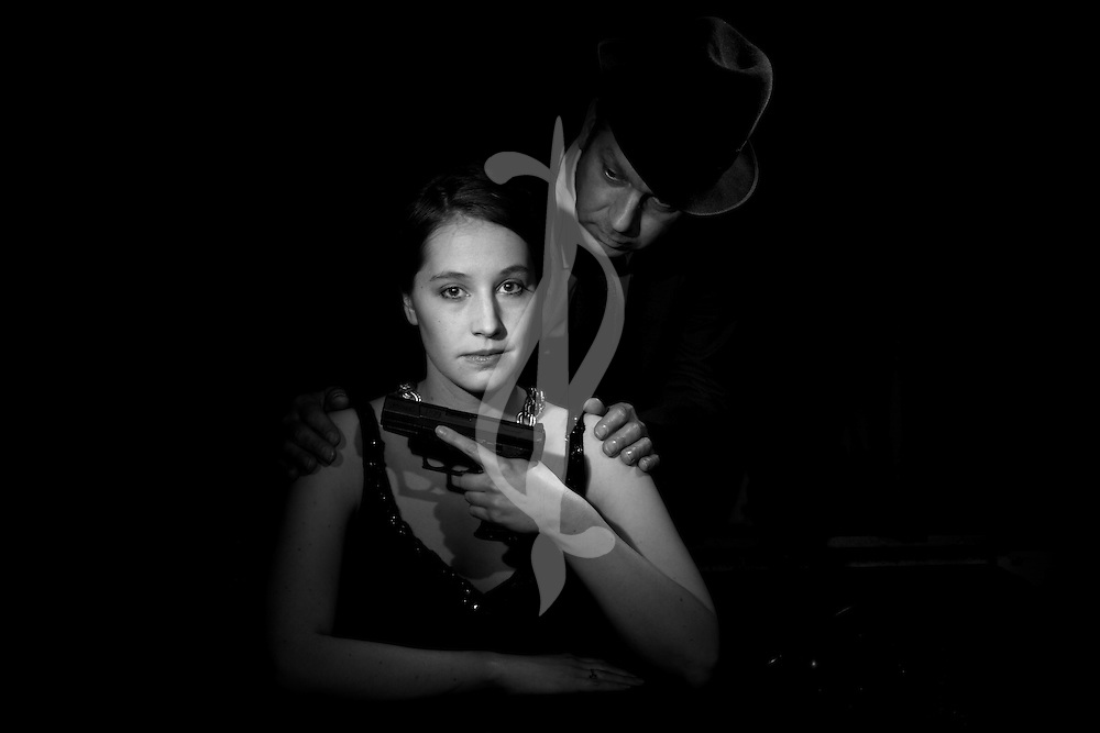 Models in retro outfits at a desk in a dark room.