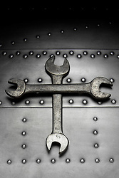 wrenches on riveted metal background