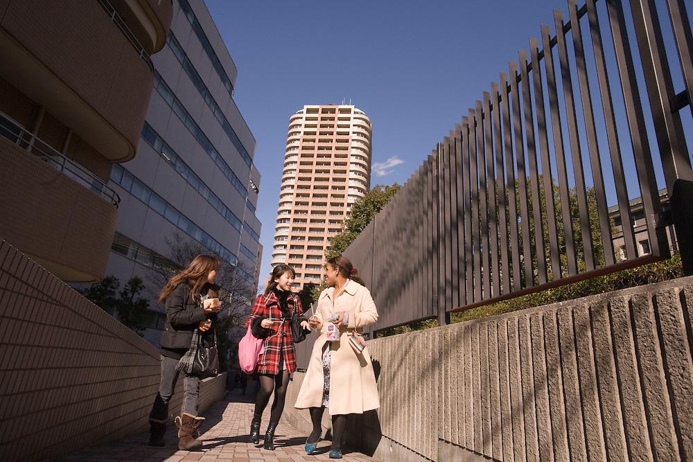 Waseda  University American and japanese students walk between classes on Nishi  Waseda  campus ..Laura Woodland (white coat,) age 20, California ; Japanese, Asian  Studies(R),  Kozue Tatsuhara, 20 Japan, liberal Arts(c)  Chelsy Crawley- 21, Hawaii ; International Business