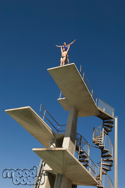 Two swimmers standing on diving board
