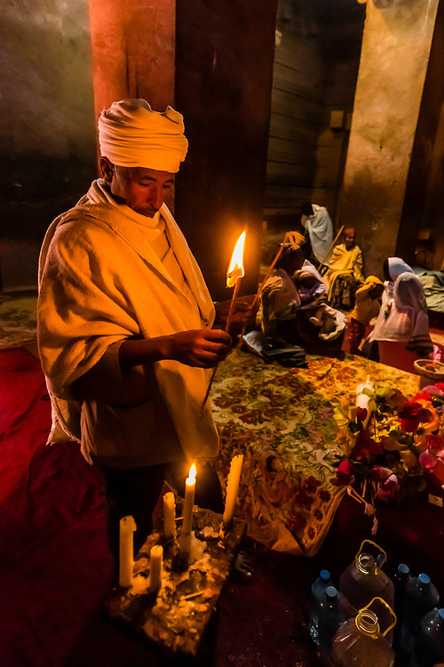 Priest lighting honey wax candles, Bet Amanuel, one of 11 rock hewn medieval monolithic churches in Lalibela, Ethiopia.