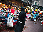 05 JULY 2011 - BANGKOK, THAILAND:   A woman from Middle East shops at a fruit stand on Soi Arab in Bangkok. Soi Arab is an alleyway in Bangkok. What started as an alley has now grown into a neighborhood that encompasses several blocks of restaurants, hotels and money exchanges that cater to Middle Eastern visitors to Thailand. The official name of the street is Sukhumvit Soi 3/1, located in North Nana between Sukhumvit Soi 3 and Sukhumvit Soi 5, not far from the Nana Plaza night-life area and the Grace Hotel popular among Arabs.   PHOTO BY JACK KURTZ