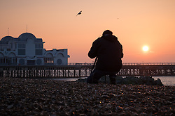 © Licensed to London News Pictures. 23/10/2016. Southsea, UK.  A photographer captures the sunrise over South Parade Pier in Southsea this morning, where the Great South Run 2016 event is being held today.  Photo credit: Rob Arnold/LNP