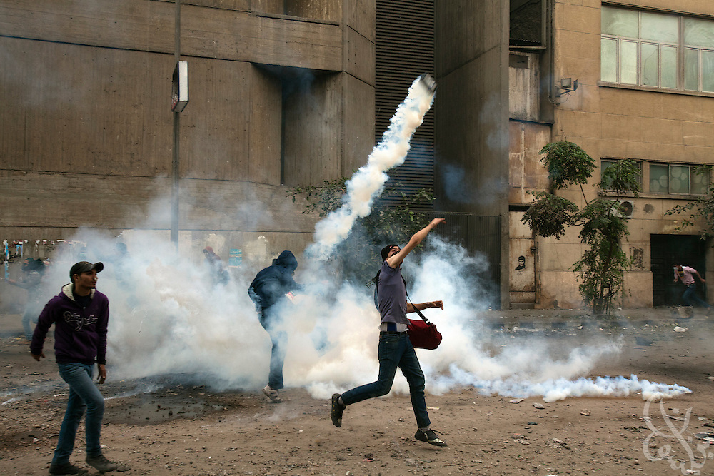 Egyptian protestors throw clear a tear gas canister fired by nearby security forces during street battles November 21, 2011 near Tahrir square  in central Cairo, Egypt. Thousands of protestors demanding the military cede power to a civilian government authority clashed with Egyptian security forces for a third straight day in Cairo, with hundreds injured and at least 24 protestors killed.  (Photo by Scott Nelson)