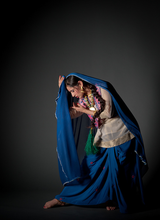 A traditional Bhangra dancer in movement in the studio