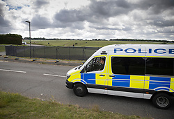© Licensed to London News Pictures. 03/07/2020. Epsom, UK. Police pass a newly erected security fence surrounding Epsom Racecourse in Surrey ahead of the running of The Derby. Tomorrow's race meeting is being held behind closed doors due to the coronavirus lockdown rules. Seven races are being held in one day including The Oaks, with The Derby being run at 17:30pm. Photo credit: Peter Macdiarmid/LNP
