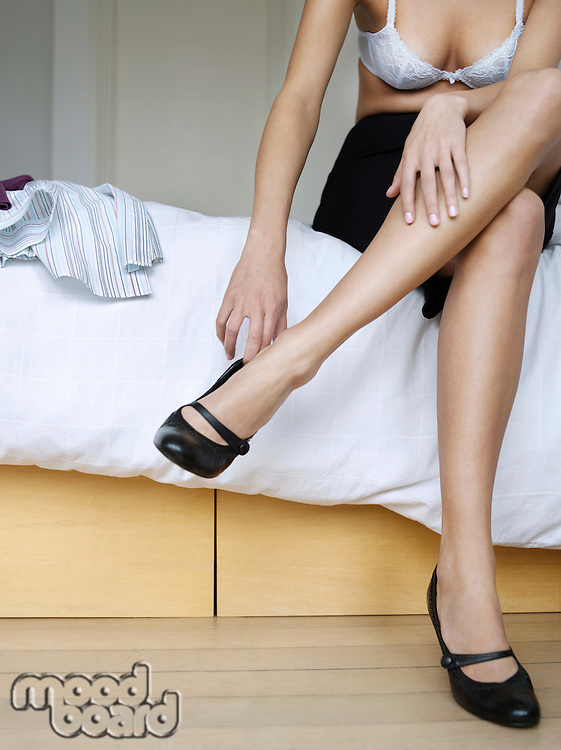 Young woman sitting on bed getting dressed low section