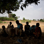 April 28, 2012 - Buram, Nuba Mountains, South Kordofan, Sudan: A Nuba family rests under the shade of a tree before continue the three to four day journey to a refugee camp in the neighbor South Sudan. Thousands of people have in the past months fled the bombardments and hunger in South Kordofan. Since the 6th of June 2011, the Sudan's Army Forces (SAF) initiated, under direct orders from President Bashir, an attack campaign against civil areas throughout the South Kordofan's province. Hundreds have been killed and many more injured...Local residents, of Nuba origin, have since lived in fear and the majority moved from their homes to caves in the nearby mountains. Others chose to find refuge in South Sudan, driven by the lack of food cause by the agriculture production halt due to the constant bombardments of rural areas.