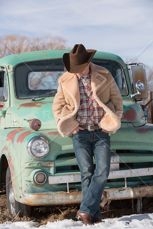 cowboy leaning up against a vintage truck