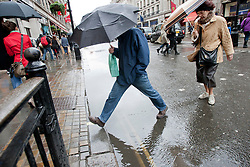 © licensed to London News Pictures. London, UK 09/04/2012. A man trying to avoid stepping in a pool on the road on Regents Street in central London, this afternoon (09/04/12). Photo credit: Tolga Akmen/LNP