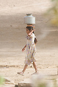 India, Rajasthan, Masuria, young girls carrying water from the well back to the village in a jug on her head