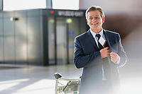 Portrait of mature attractive businessman taking out his passport from his suit in airport