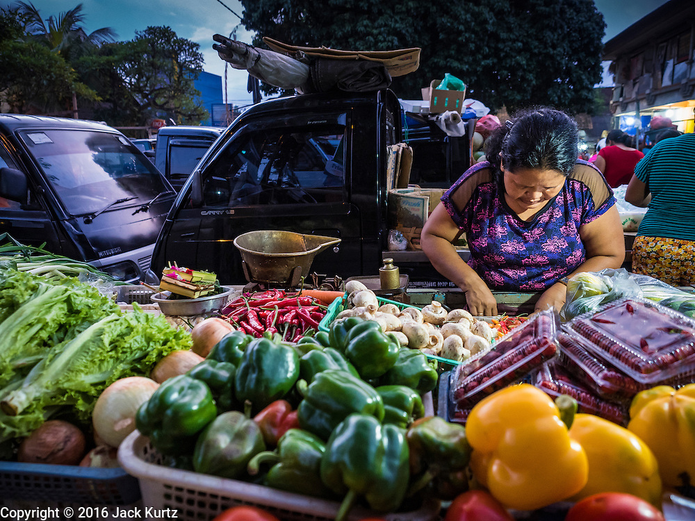 11 OCTOBER 2016 - UBUD, BALI, INDONESIA:  A produce vendor looks for change for a customer in the morning market in Ubud. The morning market in Ubud is for produce and meat and serves local people from about 4:30 AM until about 7:30 AM. As the morning progresses the local vendors pack up and leave and vendors selling tourist curios move in. By about 8:30 AM the market is mostly a tourist market selling curios to tourists. Ubud is Bali's art and cultural center.     PHOTO BY JACK KURTZ