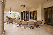 Swivel armchairs at bar area of outdoor room Palm Springs home