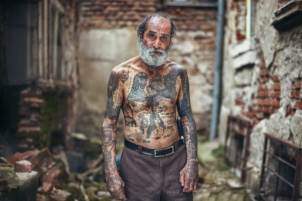 I frequently run into Pury, as he is called, at the famous Sofia market called Women's Market, located at the centre of the city. When I was taking his portrait he told me he got most of his tattoos on his body in prisons across Bulgaria. He spent half of his life in prison. His tattoos are far from perfect as the they were done by other prisoners with improvised tools and any materials they could find in the prisons. Many of his tattoos depict people who were close to him somehow, like his lovers or friends, and some of his tattoos are just drawings of different objects and symbols.<br />