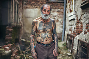 I frequently run into Pury, as he is called, at the famous Sofia market called Women&rsquo;s Market, located at the centre of the city. When I was taking his portrait he told me he got most of his tattoos on his body in prisons across Bulgaria. He spent half of his life in prison. His tattoos are far from perfect as the they were done by other prisoners with improvised tools and any materials they could find in the prisons. Many of his tattoos depict people who were close to him somehow, like his lovers or friends, and some of his tattoos are just drawings of different objects and symbols.<br /> <br /> March 2011