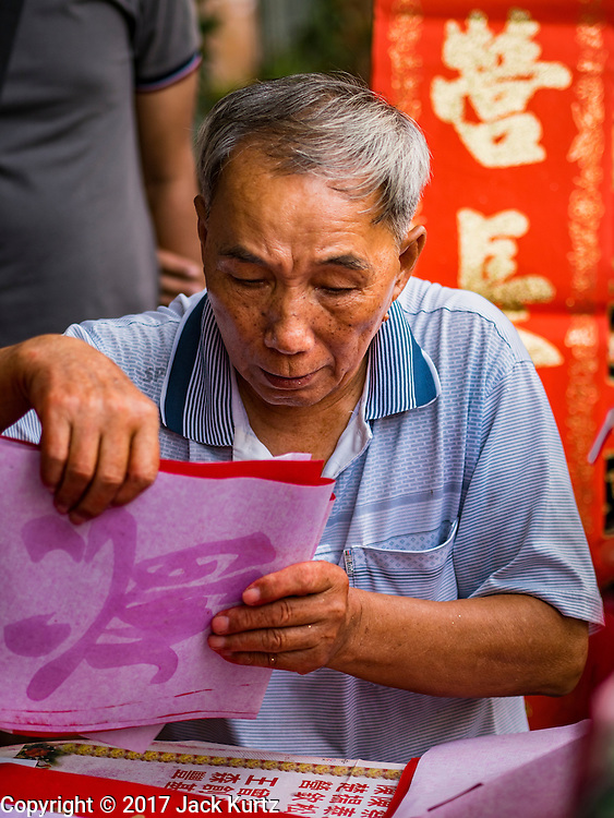 """18 JANUARY 2017 - BANGKOK, THAILAND: A Chinese calligrapher wraps up pieces of Chinese New Year calligraphy for a customer in Bangkok's Chinatown district, before the celebration of the Lunar New Year. Chinese New Year, also called Lunar New Year or Tet (in Vietnamese communities) starts Saturday, 28 January. The coming year will be the """"Year of the Rooster."""" Thailand has the largest overseas Chinese population in the world; about 14 percent of Thais are of Chinese ancestry and some Chinese holidays, especially Chinese New Year, are widely celebrated in Thailand.       PHOTO BY JACK KURTZ"""