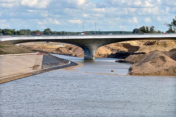 Nederland, Nijmegen, 15-9-2015De nevengeul aan de overkant van de Waal bij Lent nadert zijn voltooiing. Laatste werkzammheden. Zicht op de verlengde Waalbrug die de betonprijs won. Grootste onderdeel van de vele werken van Rijkswaterstaat om bij hoogwater een betere waterafvoer in de rivier te hebben. Het is een omvangrijk project waarbij onder meer de pijlers van het spoorviaduct een bredere basis kregen omdat die straks in de loop van het water staan. Ook de n325 die vanaf de Waalbrug naar Arnhem loopt is over 400 meter opnieuw aangelegd omdat het talud vervangen wordt door een nieuwe brug met drie gracieuze pijlers. Het dorp veurlent komt op een kunstmatig eiland te liggen met twee bruggen als ontsluiting. Een voetgangersbrug en een andere, de Promenadebrug, voor normaal verkeer. Inmiddels begint de nieuwe kade aan de noordkant van deze geul vorm te krijgen. Ruimte voor de rivier, water, waal. In de nieuwe dijk wordt een drempel gebouwd die stapsgewijs water doorlaat en bij hoogwater overloopt.The Netherlands, NijmegenMeasures taken by Nijmegen to give the river Waal, Rhine, more space to flow during highwater and to prevent the risk of flooding. Room for the river. Reducing the level, waterlevel. Large project to create a new paralel gully, an extra flow of water, so the river can drain more water during highwater. Due to climate change and expected rise, increase of the sealevel, the Dutch continue to protect their land from the water.Foto: Flip Franssen/HH