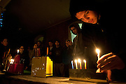 Jarrad Gold lights a menorah during a cermony held tuesday on the porch of the Alpha Epsilon Pi fraternity in celbration of the fourth night of Hanukkah. There ceremony was attended by jewish members of Alpha Epsilon Pi, Sigma Kappa sorority and Rabbi Danielle Lehaw. Also pictured (from left to right) are Rabbi Danielle Leshaw, Ruthie Leshaw, Rachel Rzepka, Lauren Devinson, Janie Silverman, Marc Hochhause, Seth Schwartz,  Joey Rosen, Risa Katz and Jacob Freeder. Photo by: Ross Brinkerhoff.